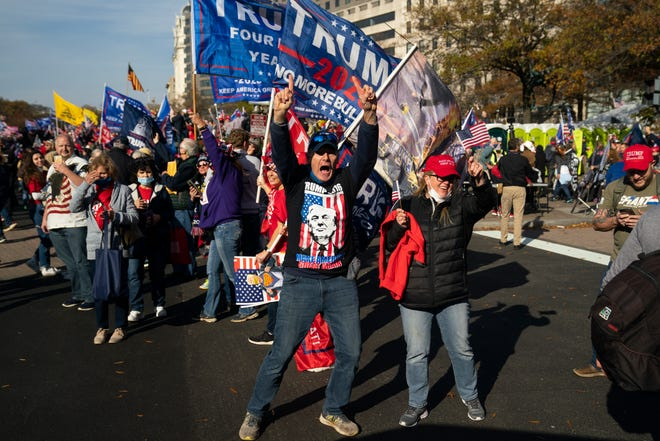 Supporters of President Donald Trump cheer as his motorcade drives past a rally of supporters near the White House on Saturday in Washington.