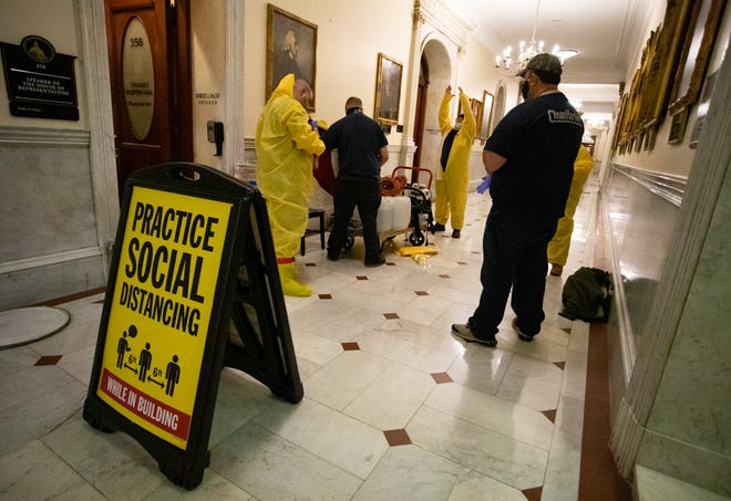 Staff members from Clean Harbors Inc., a Norwell company that offers COVID-19 decontamination and disposal services, pulled on yellow jumpsuits Friday, Nov. 13, 2020, before entering the House speaker's office.