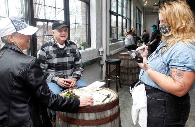 Waitress Kim Boya (right) waits on Carla and Brian Gilmartin of Auburn during the grand opening of the Medusa Brewing Company at the Landing at Hudson Mills, Nov. 14, 2020.