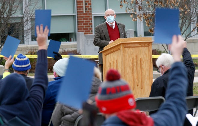 Hudson Moderator Richard Harrity watches as residents vote on an article during the Special Town Meeting, held outside in the parking lot of Hudson High School due to the COVID-19 pandemic, on Saturday, Nov. 14, 2020.