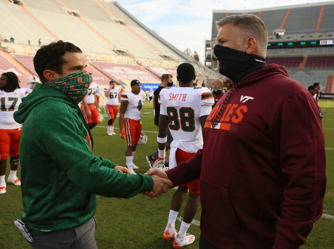 Virginia Tech coach Justin Fuente, right, and Miami coach Manny Diaz meet at midfield after Miami's 25-24 win Saturday. Numerous Hurricanes players were out due to COVID-19 issues, and now the Canes' next two games have been postponed.