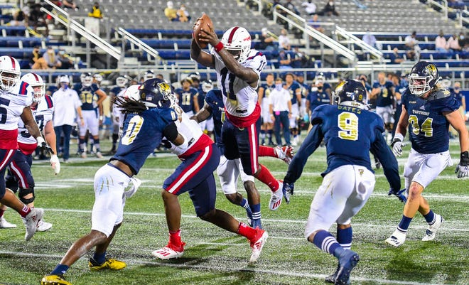 Florida Atlantic Owls quarterback Javion Posey (11) leaps for a touchdown during a 38-19 win over the Florida International Panthers in the Shula Bowl in Miami on Friday.