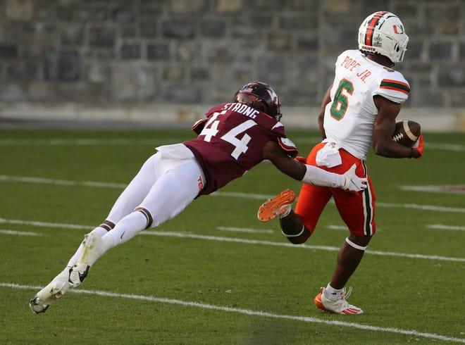 El receptor abierto de Miami, Mark Pope Jr., supera al back defensivo de Virginia Tech, Dorian Strong, en su camino hacia el touchdown ganador del juego en el último cuarto en Lane Stadium en Blacksburg, Virginia.