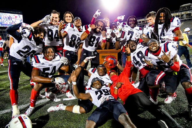 Florida Atlantic head coach Willie Taggart (red shirt) celebrates with his team after defeating the FIU Panthers, 38-19, in the Shula Bowl in Miami on Friday.