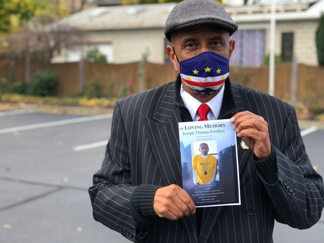 Jim Vincent, president of the NAACP Providence Branch, holds a funeral service program with a photo of Joseph Fowlkes, a former president of the organization who died last month.