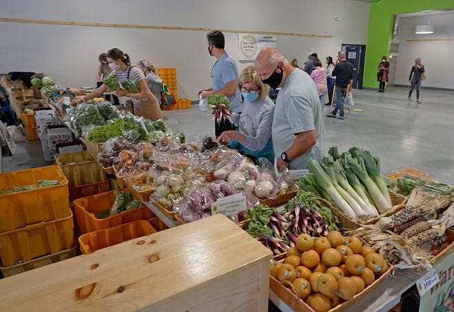 Shoppers at the re-located Farm Fresh Winter Market check out the produce at the Ward's Berry Farm stand.  It's located at the  corner of Sims and Kinsley Avenues in Providence in Farm Fresh's new food hub.