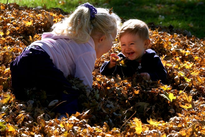 Then-1-year-old Grace Salazar of Stockton, right, plays with her cousin Megan Falkner of Temecula in a pile of fall leaves at Grupe Park in Stockton in 2003.