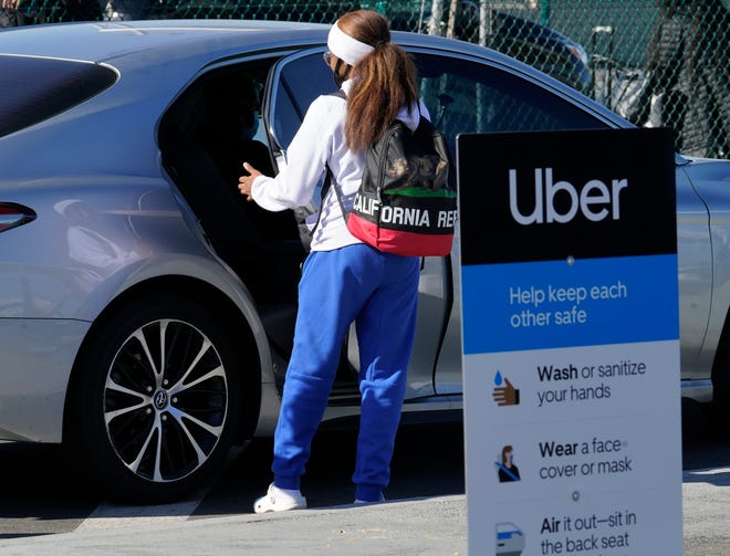 A traveler rides in the back of an Uber vehicle at Los Angeles International Airport on Friday, when the governors of California, Oregon and Washington issued travel advisories, urging people entering their states or returning from outside the states to self-quarantine to slow the spread of the coronavirus.