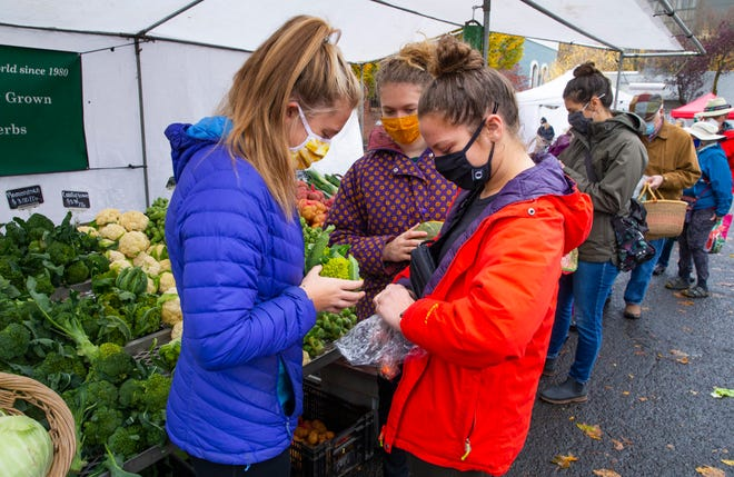 University of Oregon students Shae Boos, left,  Siena Dorman  and August Lewis-Hoogerhuis gather produce during a visit to the Lane County Farmers Market in Eugene.