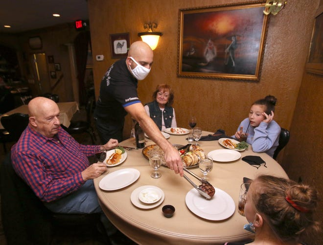 Joe Shaheen, manager and bartender at the Desert Inn, serves (from left) Bob and Judith Steele and their grandchildren, Elena and Emily Steele in Canton, on Saturday.