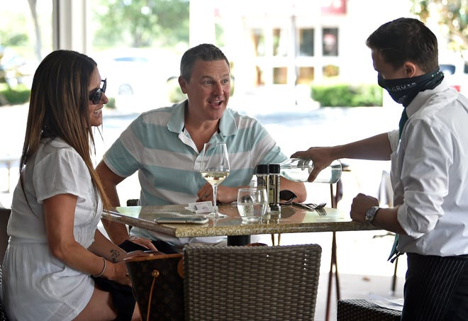 Alex Blatt serves Ken and Tara Broderick in May at Grove in Lakewood Ranch. Grove is one of many restaurants we recommend in Sarasota and Manatee counties open Christmas Day with dine-in and to-go options.