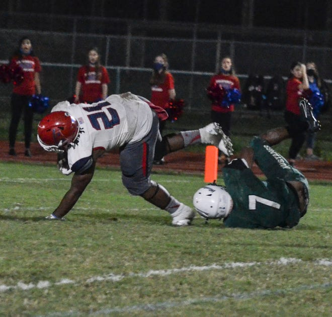 Manatee running back Kyree Jones keeps his balance after being hit by Lakewood Ranch's Eli Daniels during Friday's Class 7A play-in game. Jones gained 115 yards and scored two touchdowns in the Hurricanes' 51-14 victory.