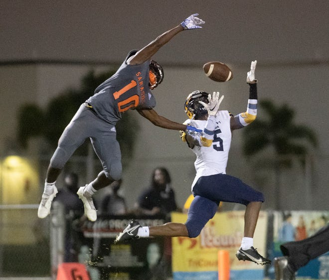 Sarasota High's T.J. Mckay (10) breaks up a pass to Lehigh Acres's Tar'varish Dawson (5) during Friday night's playoff game at Ihrig Field in Sarasota.