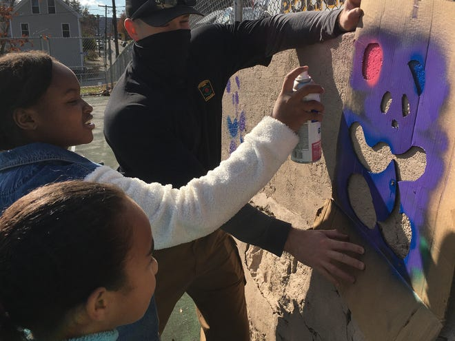 Norwich police Officer Bob McKinney helps out Alana Veale, 10, and Jalaya Duarte-Robinson, 11, during a beautification project at the Greeneville playground on Saturday.