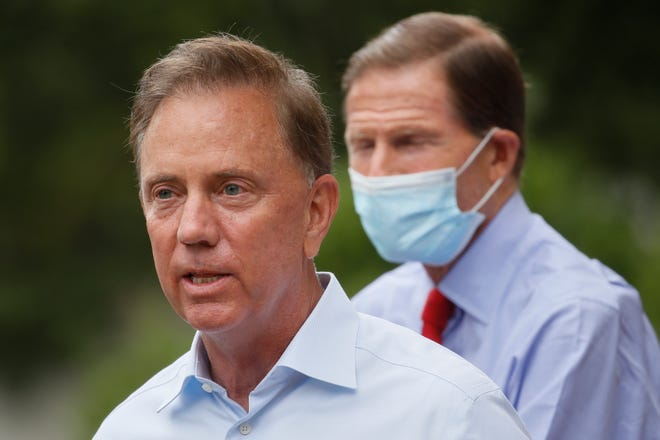 Connecticut Gov. Ned Lamont speaks to reporters before surveying storm damage in the area in Westport, Conn. Connecticut Gov. Ned Lamont is self-quarantining after his chief spokesperson tested positive for COVID-19, his administration announced late Friday. [AP Photo/John Minchillo, File]