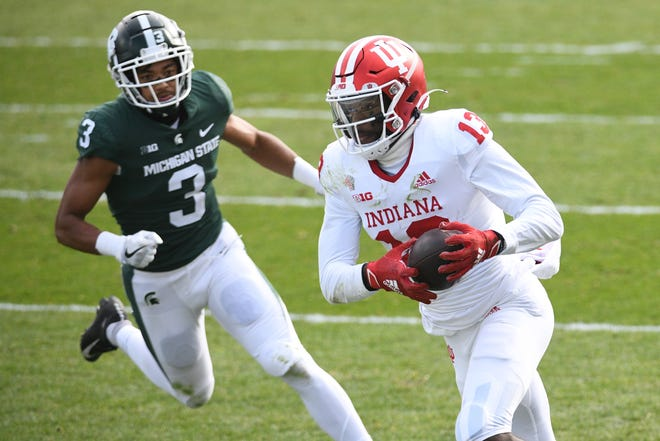 Indiana wide receiver Miles Marshall runs the ball as Michigan State safety Xavier Henderson pursues during the first half Saturday at East Lansing, Michigan.