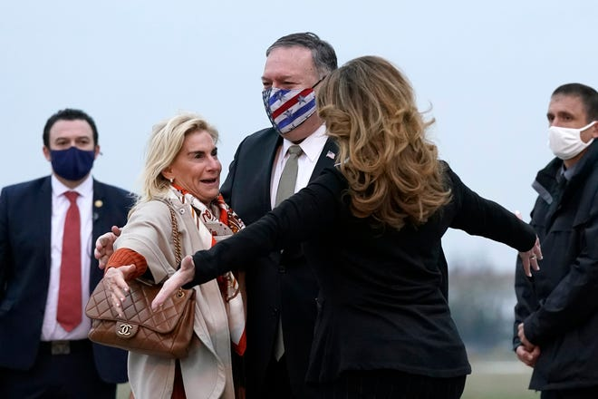 U.S. Secretary of State Mike Pompeo, center, and his wife, Susan, right, embrace U.S. Ambassador to France Jamie McCourt, left, after stepping off a plane Saturday at Paris Le Bourget Airport.
