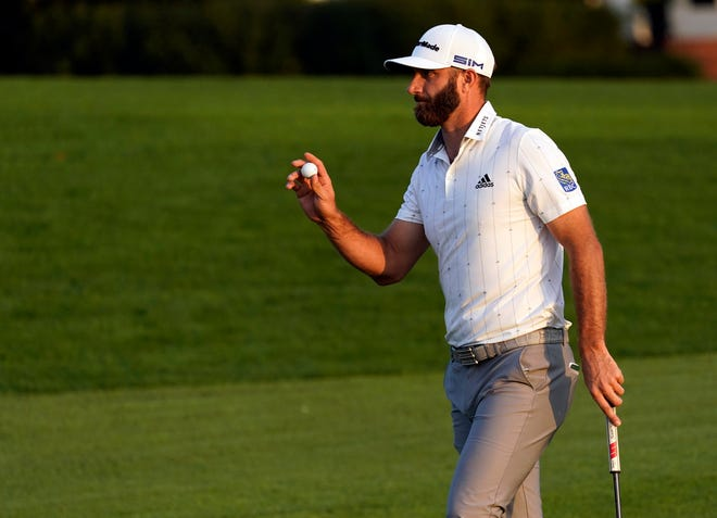 Dustin Johnson waves after putting out on the 18th green during the third round of the Masters at Augusta National GC.