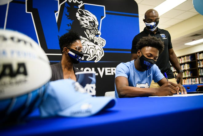 With his mother, Veronica Johnson, and coach George Stackhouse watching, WestoverÕs DÕMarco Dunn signs his letter of intent to play basketball at UNC on Friday, Nov. 13, 2020, at a small ceremony at Westover High School.