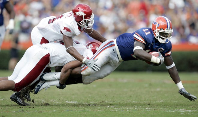 Arkansas players John Jackson and Darius Vinnett bring down Florida's O.J. Small in the third quarter of the Oct. 2, 2004 game at Ben Hill Griffin Stadium.