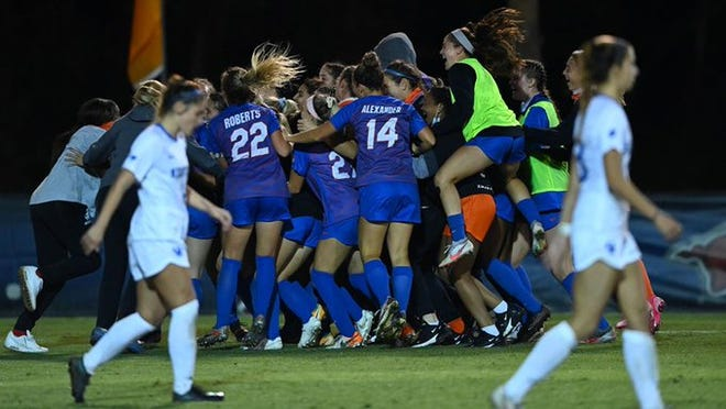 Florida's soccer team celebrates the OT win Friday night over Kentucky in the SEC tourney in Alabama.