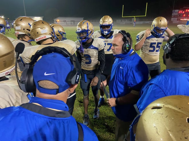 Head coach Scott Wilson gives Daytona Beach Mainland instructions during a third quarter timeout in Friday night's Region 1-6A playoff game vs. Gainesville High.