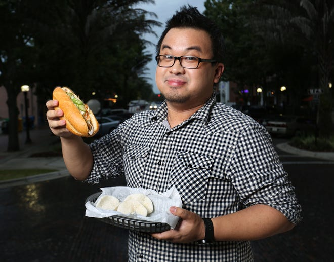 Ken Peng, who writes the Ken Eats Gainesville food blog, eats a sandwich from The Lunchbox outside the Hippodrome in downtown in Gainesville Oct. 13, 2014.