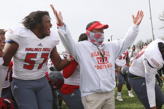 Walnut Ridge's Ras Anderson laughs after he and others dumped a cooler of ice water on coach Byron Mattox to celebrate their 14-6 win over Eastmoor Academy in the City League championship game Nov. 14 at Africentric.