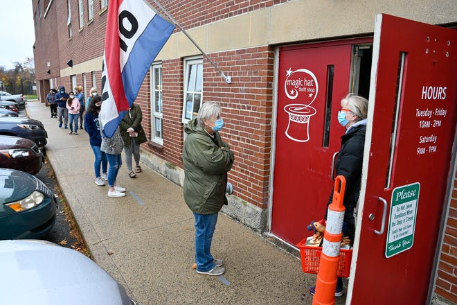 A line of people wait outside the Magic Hat Thrift Shop, located at the Marblehead Middle School, which just re-opened after being closed for nine months due to the coronavirus pandemic, Friday, Nov. 13, 2020.
