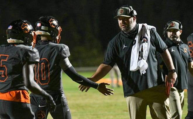 "Cocoa football head coach Ryan Schneider, shown here congratulating quarterback D.J. Arroyo after a touchdown, said he's ""praying"" that colleges offer more scholarships before National Signing Day in February. Craig Bailey/FLORIDA TODAY via USA TODAY NETWORK"