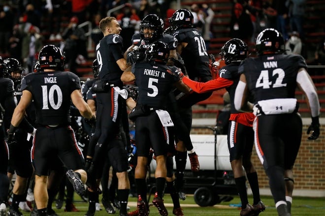 The Cincinnati Bearcats celebrate a touch down reception by wide receiver Michael Young Jr. (8) in the second quarter of the NCAA American Athletic Conference football game between the Cincinnati Bearcats and the East Carolina Pirates at Nippert Stadium in Cincinnati on Friday, Nov. 13, 2020. The Bearcats led 35-10 at halftime.