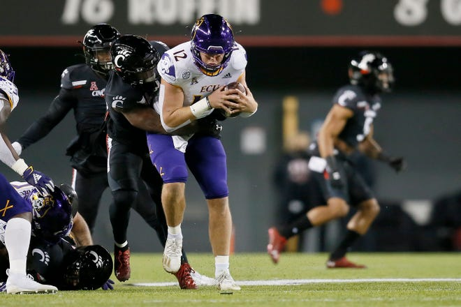 East Carolina Pirates quarterback Holton Ahlers (12) is sacked by Cincinnati Bearcats linebacker Jarell White (8) in the first quarter of the NCAA American Athletic Conference football game between the Cincinnati Bearcats and the East Carolina Pirates at Nippert Stadium in Cincinnati on Friday, Nov. 13, 2020. The Bearcats led 35-10 at halftime.