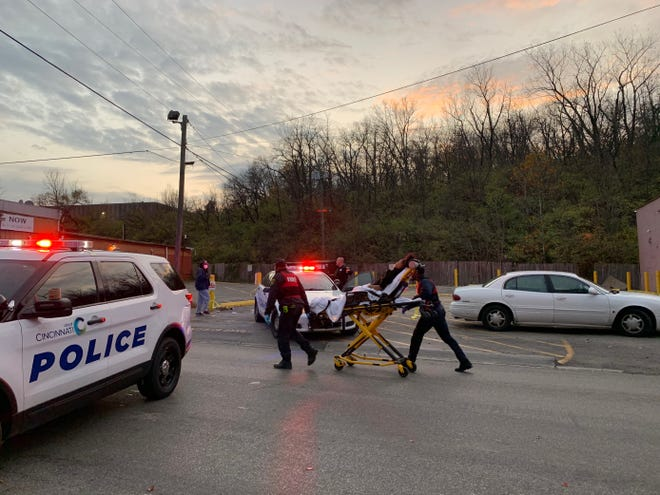 Medics responding to a shooting on Kings Run Drive in Cincinnati transport a victim by stretcher on Saturday, Nov. 14, 2020.