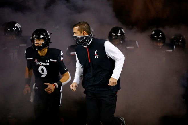 University of Cincinnati football coach Luke Fickell and quarterback Desmond Ridder lead the Bearcats onto the field at Nippert Stadium on Friday, Nov. 13, 2020.