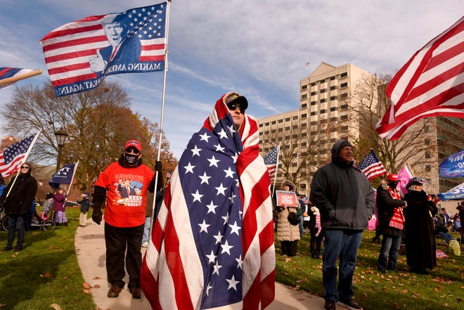 """Michael Foy of Wixom wraps himself in the flag in the chill outside as President Donald Trump supporters gather at the state Capitol Building  in Lansing for a """"Stop the Steal"""" rally disputing the presidential voting Saturday, October 14, 2020."""