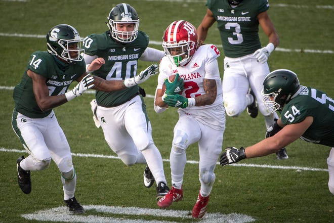 EAST LANSING, MI - NOVEMBER 14: Davion Williams #14 of the Michigan State Spartans, Jude Pedrozo #40 of the Michigan State Spartans and Jack Henrichs #54 of the Michigan State Spartans close in on Jamar Johnson #22 of the Indiana Hoosiers during the fourth quarter at Spartan Stadium on November 14, 2020 in East Lansing, Michigan. (Photo by Nic Antaya/Getty Images)
