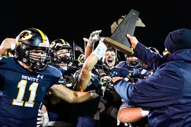 DeWitt celebrates winning the Division 3 district football championship by beating Mason 43-0 on Friday, Nov. 13, 2020, at DeWitt High School.
