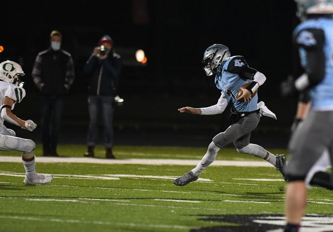 Lansing Catholic QB Joey Baker gains yardage on a QB keeper against Olivet Friday, Nov. 13, 2020, during the district final at Lansing Catholic.  The Cougars beat Olivet 17-6.
