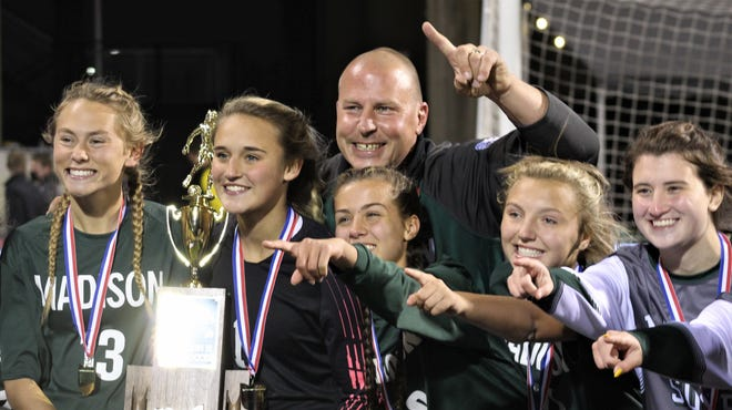 Goalie Paige Eldridge holds the championship trophy as she celebrates Madison's Division II state soccer championship with head coach Zac Huff and some of her teammates, including All-American Taylor Huff (3).