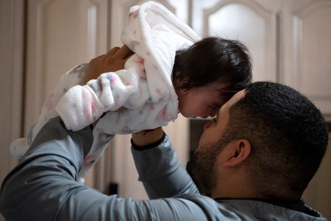 Eduardo Argueta holds his daughter Emma at Luz Vanegas' home in North Bergen on Friday, November 13, 2020. Vanegas' life turned upside down this summer when her daughter, Estefania, gave birth to her first grandchild and suffered a heart attack during delivery leaving her in a coma. Vanegas not only worried about her daughter, but also began to take care of her new granddaughter, Emma, while her father works and they figure out what happened to Estafania. Meanwhile, Vanegas is also facing deportation.