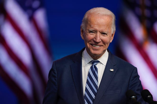 President-elect Joe Biden pauses to smile as listens to media questions at The Queen theater on Tuesday, Nov. 10, 2020, in Wilmington.