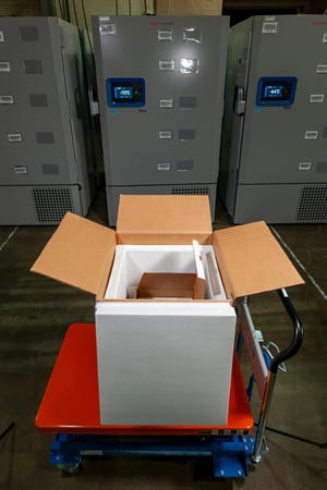 Pfizer's COVID-19 vaccine is being shipped in specially designed, insulated containers that hold between 195 and 975 five-dose vials and are about the size of a carry-on suitcase. The vials are stored in flat, pizza box-sized compartments, each of which holds 195 vials. A fully-loaded thermal container, which is reusable, contains five of these and weighs about 70 pounds.