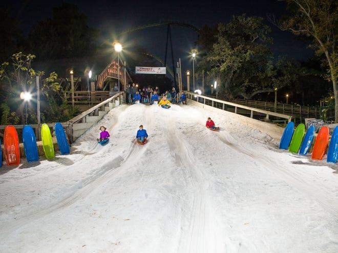 Pengunjung di Six Flags Over Texas dapat menikmati naik eretan di Frosty Snowhill di Holiday in the Park.