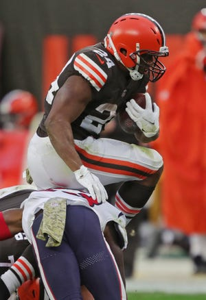 Browns running back Nick Chubb (24) hurdles a host of Houston Texans players during the second half Sunday in Cleveland.