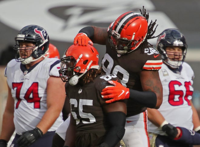 Cleveland Browns defensive tackle Larry Ogunjobi (65) is congratulated by Cleveland Browns defensive tackle Sheldon Richardson (98) after sacking Houston Texans quarterback Deshaun Watson (4) during the first half of an NFL football game, Sunday, Nov. 15, 2020, in Cleveland, Ohio. [Jeff Lange/Beacon Journal]