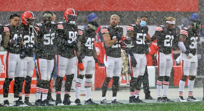 Browns players brave the elements during the national anthem before Sunday's game against the Houston Texans in Cleveland.