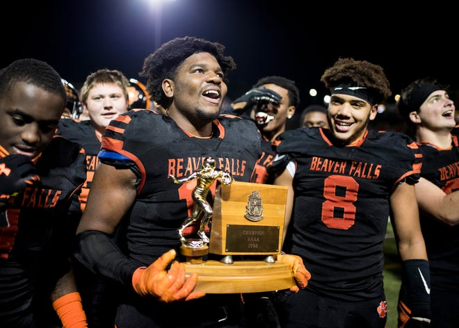 Beaver Falls' Josh Hough holds the trophy after the Tigers defeated Sto-Rox 43-30 to clinch the WPIAL Class 2A Championship Saturday night at Martorelli Stadium.