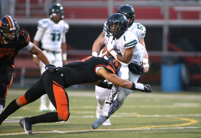 Sto-Rox's Zay Davis (7) gets taken down by Beaver Falls Tyler Cain (8) during the first half of the WPIAL 2A Championship game Saturday night at Martorelli Stadium.