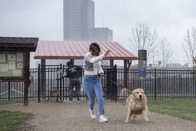 Alex Pepper, 15, and her father, Paul Pepper, of Clintonville make a run for their car in a sudden downpour at the Scioto Audubon Metro Park on Sunday.