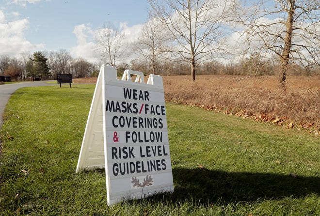 A sign reminds visitors to wear masks at Sharon Woods Metro Park in Westerville on Sunday. The Columbus and Franklin County Metro Parks announced Sunday on social media that wearing masks would be a requirement for visitors over ten years old while using the metro parks, effective Monday. Social distancing guidelines limit gatherings and groups to 10 people or fewer.